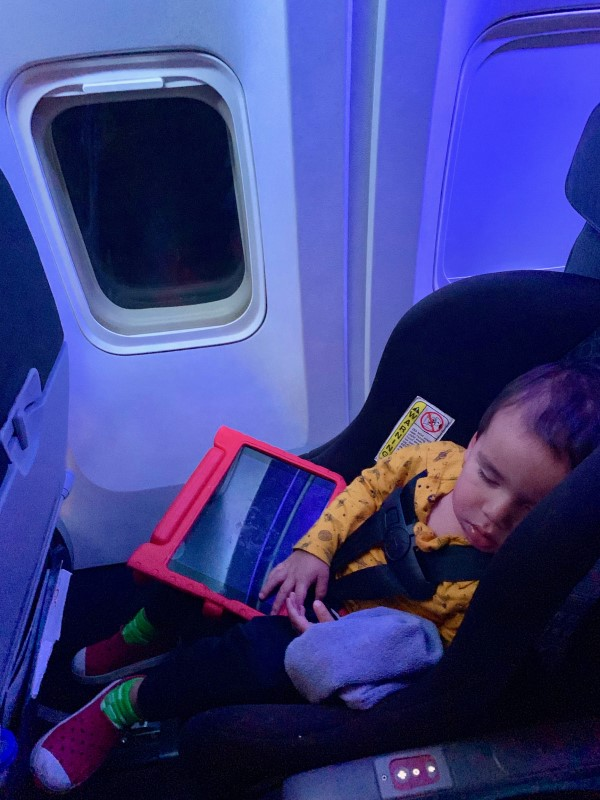 toddler sleeping plane in a car seat