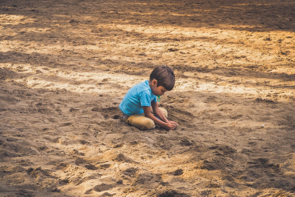 boy playing on his own in the sand